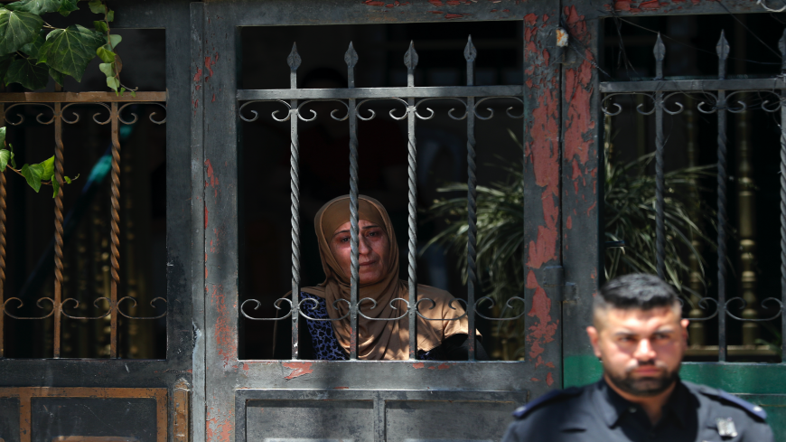 An Israeli policeman stands outside the former house of the Palestinian Siyam family as a member looks from a gate, during their eviction in the Palestinian neighbourhood of Silwan in east Jerusalem near the Old City on July 10, 2019.