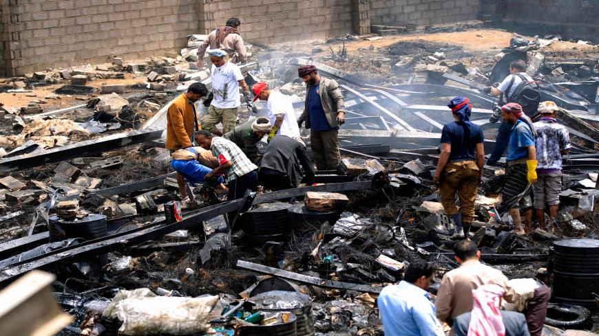 Workers search through debris at a warehouse, after it was reportedly hit in an airstrike by the Saudi-led coalition, Sanaa, Yemen, July, 2, 2020.