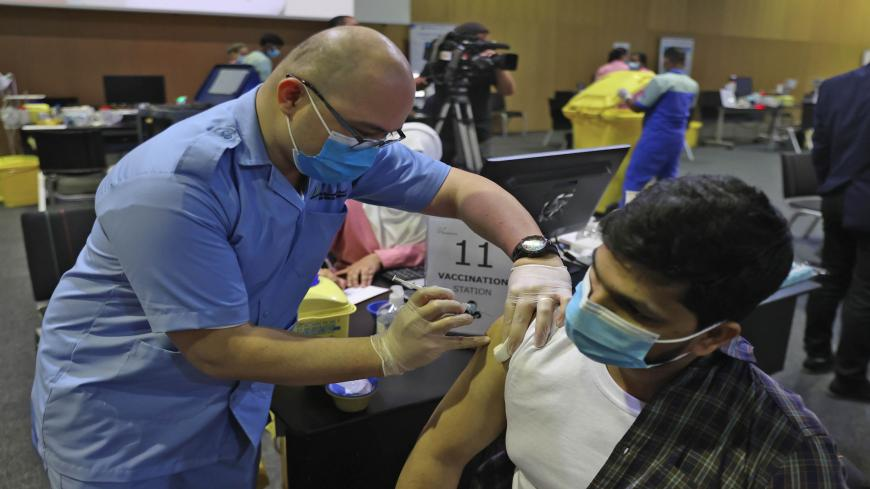 A man receives a dose of the coronavirus vaccine at the Qatar National Convention Center, Doha, Qatar, Feb. 18, 2021.