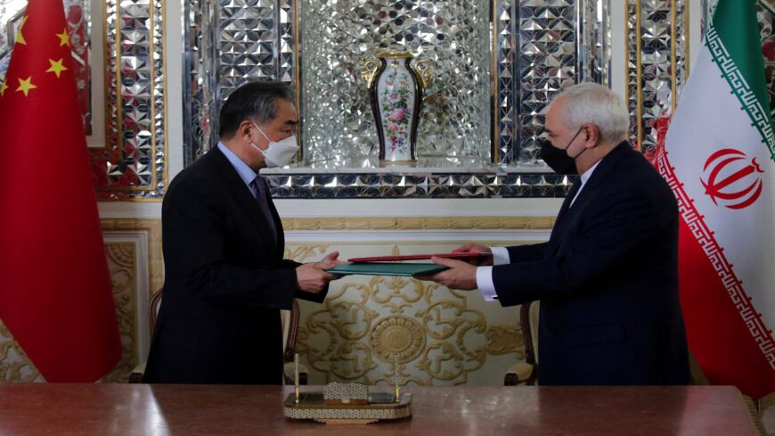 "Iranian Foreign Minister Mohammad Javad Zarif (R) and his Chinese counterpart, Wang Yi, are pictured during the signing of an agreement in the capital, Tehran, on March 27, 2021. Iran and China signed what state television called a ""25-year strategic cooperation pact,"" as the US rivals move closer together."