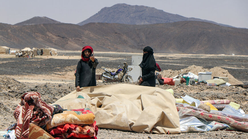 Women wait next to belongings at a camp for the internally displaced about 10 kilometres on the outskirts of Yemen's northeastern city of Marib on March 28, 2021, as residents of the camp prepare to flee due to its proximity with battles between forces of the Houthi-rebels and the Saudi-backed government troops.