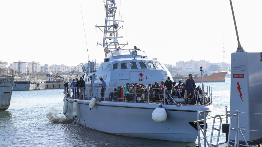 Migrants arrive at a naval base in the Libyan capital of Tripoli