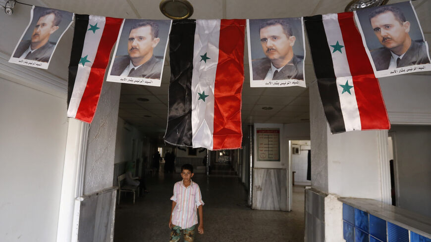 A Syrian boy walks under portraits of Syrian President Bashar al-Assad adorning a hospital in the eastern city of Deir Ezzor on Sept. 20, 2017.