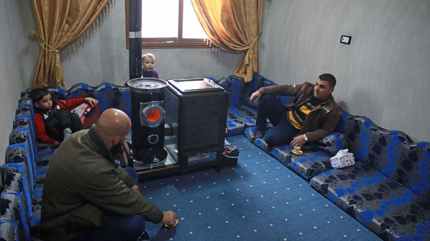 Abu Walid warms his living room with a pistachio-powered heater in Tal al-Karama village, in northwestern province of Idlib, Syria, Dec. 6, 2019.