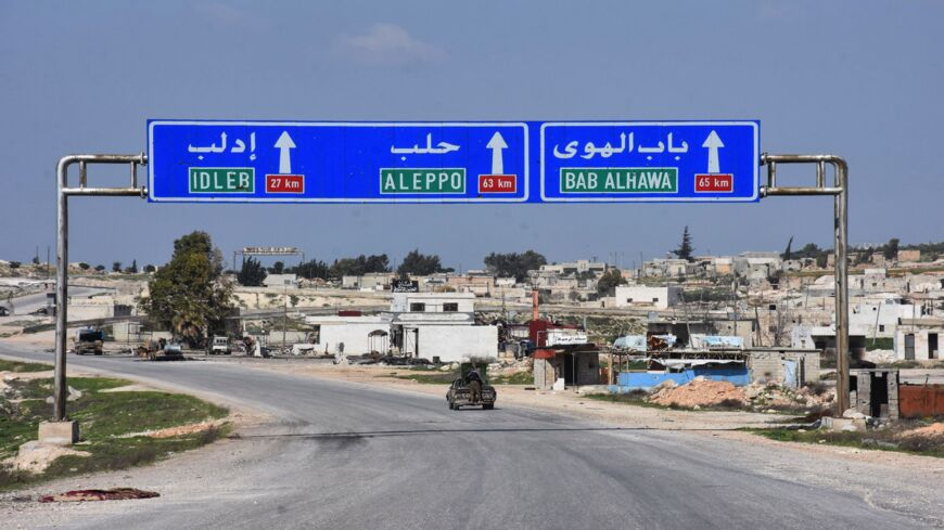 Syrians drive in the town of Saraqeb along the main Damascus-Aleppo (M5) highway in Syria's northwestern Idlib province on March 7, 2020, following a Russian-Turkish cease-fire deal.