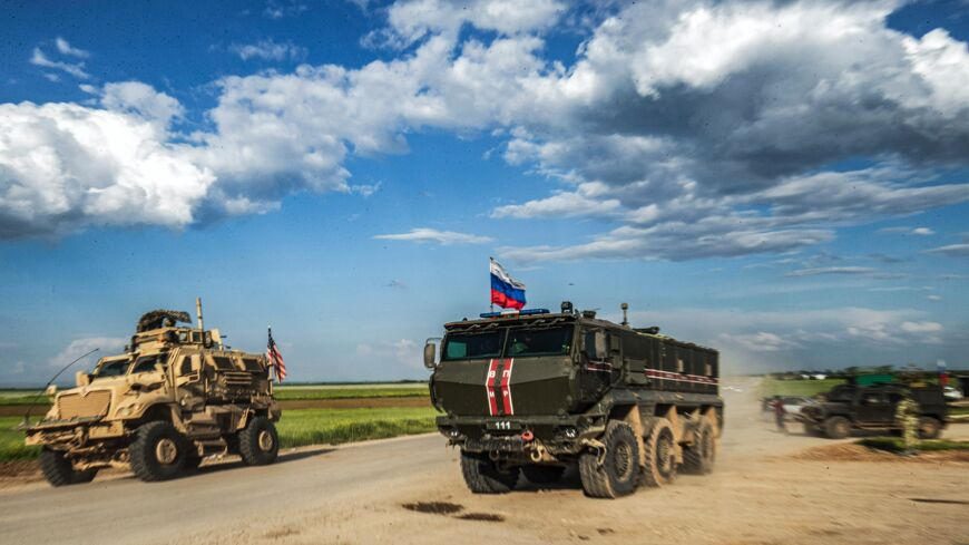 A Russian military police armored truck drives past a US military MRAP (Mine Resistant Ambush Protected) vehicle near the village of Tannuriyah in the countryside east of Qamishli in Syria's northeastern Hasakah province on May 2, 2020.