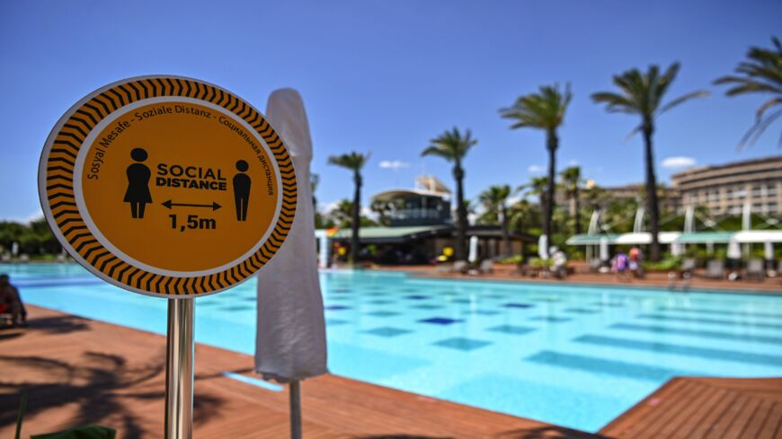 "A sign reads ""Social distance 1.5m"" next to the pool of a hotel on June 19, 2020, at Lara district in Antalya, a popular holiday resort in southern Turkey. The novel coronavirus pandemic has hit Turkey's tourism industry, the backbone of the country's economy."
