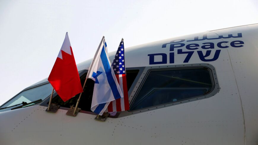 "The Bahraini, Israeli and US flags are pictured attached to the Boeing 737 aircraft of Israel's El Al, adorned with the word ""peace"" in Arabic, English and Hebrew, ahead of the flight to Bahrain's capital, Manama, at Israel's Ben Gurion Airport near Tel Aviv on Oct. 18, 2020."