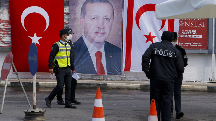 Turkish Cypriot police stand before a portrait of Turkish President Recep Tayyip Erdogan in the disputal coastal town of Varosha, in Famagusta, Cyprus, Nov. 15, 2020.