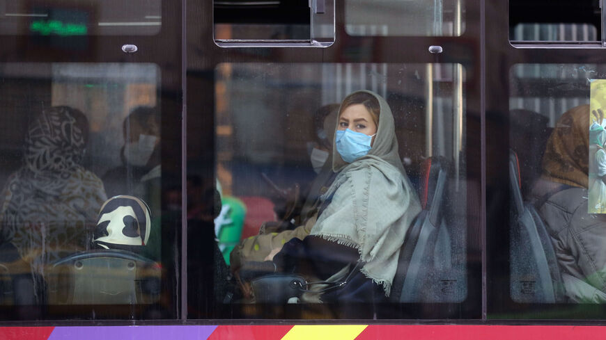 An Iranian woman wearing a protective mask amid the COVID-19 pandemic, sits in a bus in the capital Tehran, on Dec. 30, 2020.