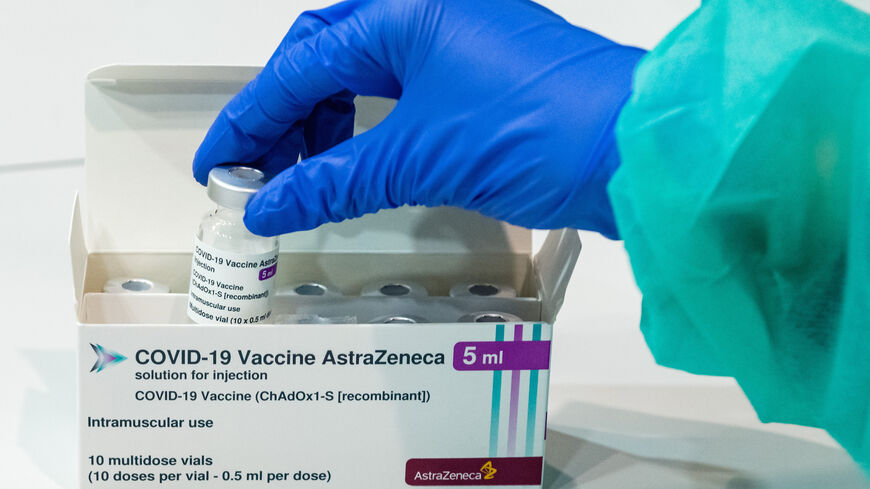 Medical staff handle an empty vial of the AstraZeneca vaccine against COVID-19 at a vaccination center at the Messe trade fair grounds during the third wave of the coronavirus pandemic on April 8, 2021 in Erfurt, Germany.