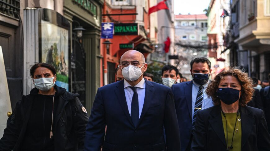 Greece's Foreign Minister Nikos Dendias (C) walks on Istiklal Avenue after his meeting with the Patriarch of Constantinople at the Greek Consulate in Istanbul on April 14, 2021.
