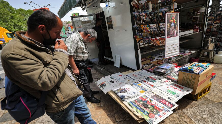 Men view the covers of local newspapers laid out at a stall in the Shemiran district of Iran's capital, Tehran, on April 14, 2021. Iran warned it would start enriching uranium up to 60% purity after an explosion it blamed on archenemy Israel hit its key nuclear facility in Natanz.