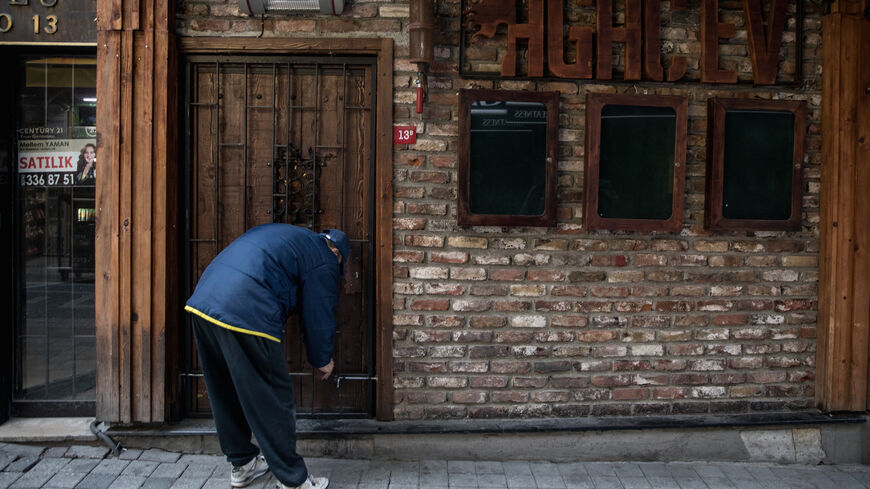 An employee of Agac Evi Blues Bar locks the bars front door after checking the inside after the venue has been closed for nearly a year due to coronavirus restrictions on February 24, 2021 in Istanbul, Turkey.