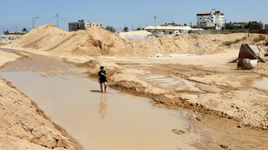 A Palestinian man walks in a pool of water next to the entrance of tunnels, used for smuggling supplies between Egypt and the Gaza Strip, Rafah, Gaza Strip, Sept. 18, 2015.