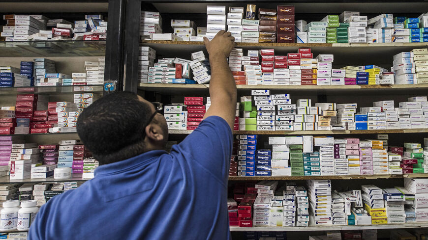 A pharmacy employee reaches out to grab a box of medicine in a pharmacy, Cairo, Egypt, Nov. 9, 2016.