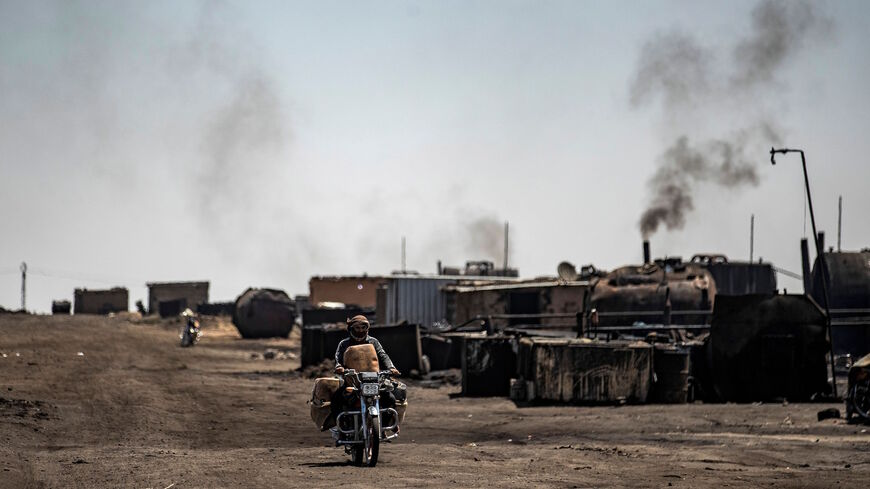 A man drives a motorcycle past a makeshift refinery using burners to distill crude oil in the village of Bishiriya in the countryside near the town of Qahtaniya west of Rumaylan (Rmeilan) in Syria's Kurdish-controlled northeastern Hasakeh province, on July 19, 2020.