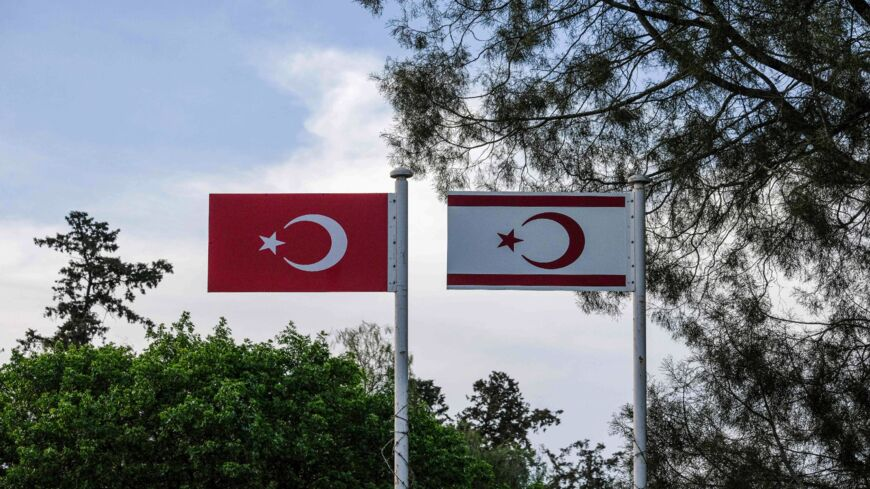 A picture taken from the Greek-Cypriot side of the divided Cypriot capital Nicosia on April 24, 2021, shows metal flags of Turkey (L) and the self-declared Turkish Republic of North Cyprus (TRNC), recognized only by Ankara, above the Turkish-controlled side of the divided capital.