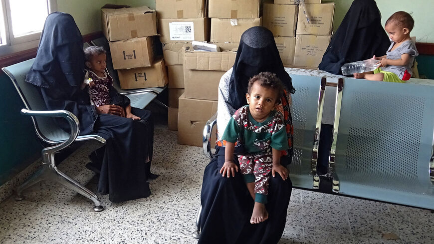 Yemeni women wait with their malnourished children ahead of treatment sessions at a medical center in Yemen's war-ravaged western province of Hodeida, on April 24, 2021.