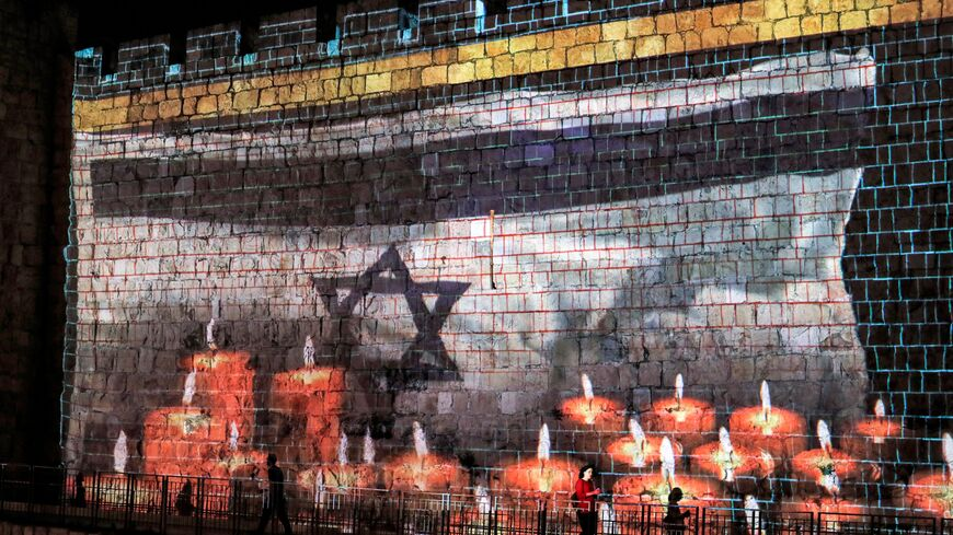 A projection of an Israeli flag flying before lit candles is displayed on the Old City walls of Jerusalem, as Israel declares a national day of mourning for victims of a stampede during the Lag Ba'Omer holiday at Mount Meron, May 2, 2021,