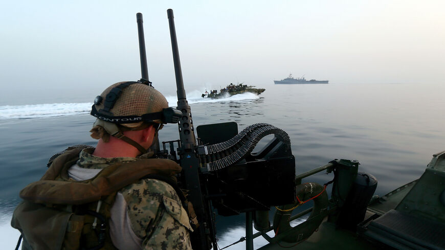 A US Navy personnel mans a heavy machine gun as he watches a Riverine Command Boat (C) cruising past the USS Ponci in the Arabian Sea, on the first day of the the biggest mine countermeasures exercise in the Arabian Gulf, May 13, 2013.