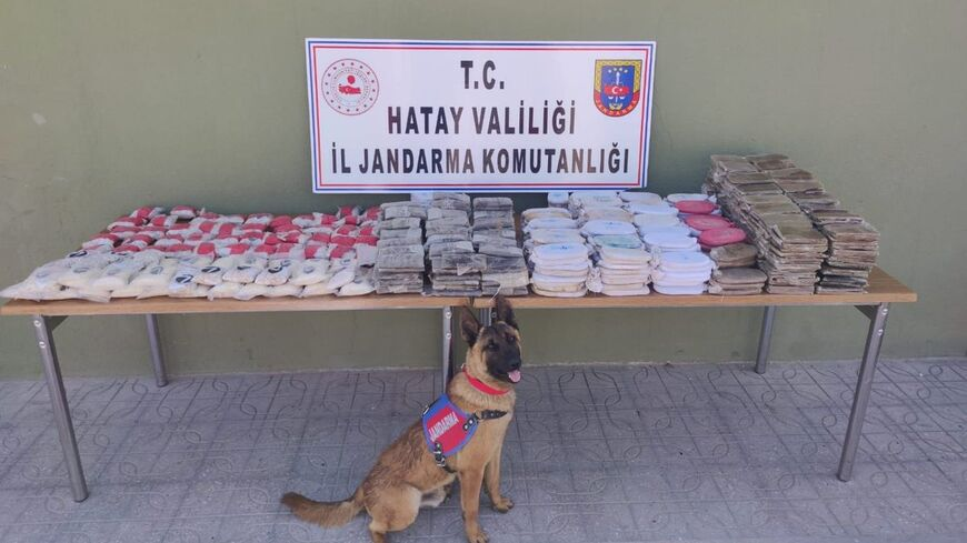 A sniffer dog poses in front of 84,000 captagon pills and other narcotics seized in Hatay, Turkey, June 8, 2021. (TWITTER/HaberHty)