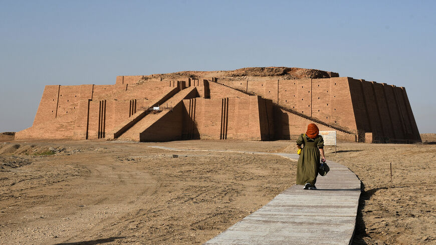 A woman walks toward the Great Ziggurat Temple, a massive Sumerian stepped mudbrick construction dedicated to the moon god Nanna that dates back to 2100 B.C. in the ancient city of Ur, Dhi Qar province, Iraq, June 15, 2020.