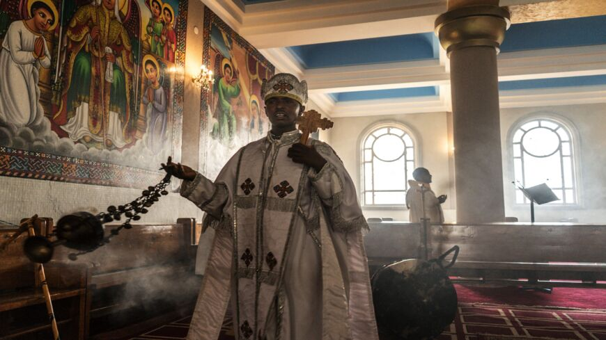 An Ethiopian Orthodox priest wafts incense during a prayer inside Bole Medhanialem church in Addis Ababa, Ethiopia, on June 20, 2021.