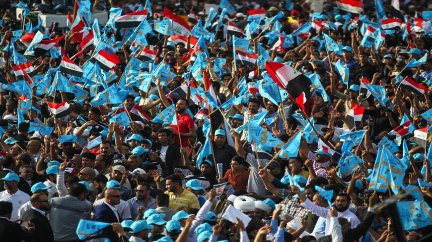 """Iraqi supporters of Shiite leader Muqtada al-Sadr raise flags of their """"Marching Toward Reform"""" electoral alliance during a campaign rally in the capital, Baghdad, on May 4, 2018."""