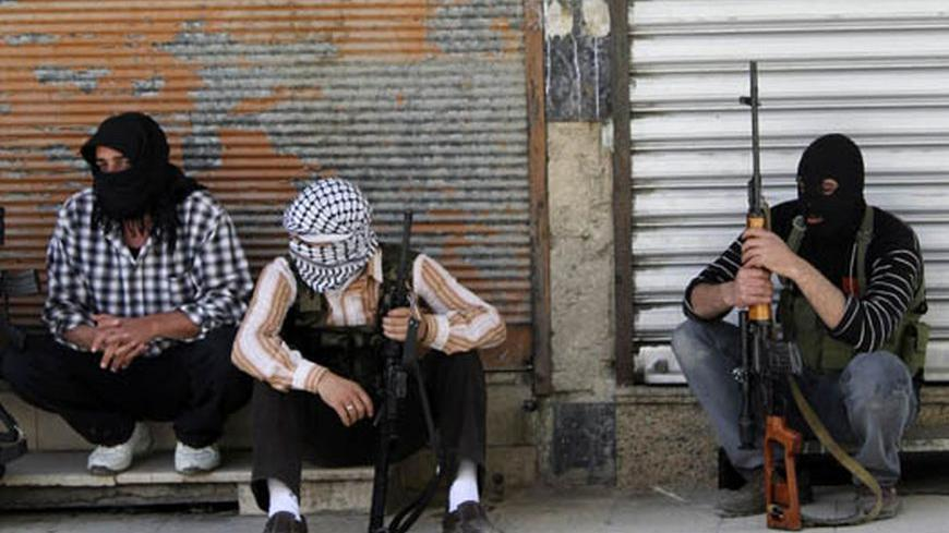 Free Syrian Army members, with covered faces and holding weapons, sit by the side of a street in Qaboun district, Damascus June 11, 2012. REUTERS/Stringer     (SYRIA - Tags: CIVIL UNREST POLITICS MILITARY)