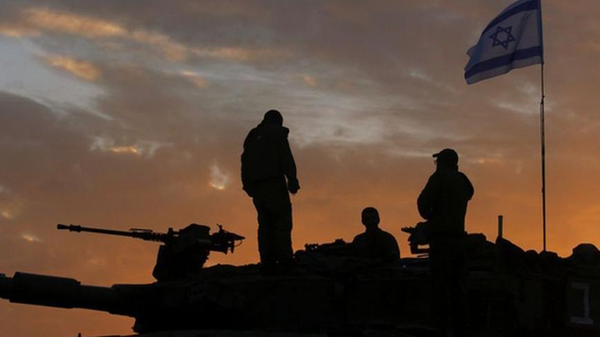 Israeli soldiers, atop a tank, prepare to leave their Gaza border position at sun rise November 22, 2012. A ceasefire between Israel and Gaza's Hamas rulers took hold on Thursday after eight days of conflict, although deep mistrust on both sides cast doubt on how long the Egyptian-sponsored deal can last.  REUTERS/Yannis Behrakis (ISRAEL - Tags: CONFLICT POLITICS)