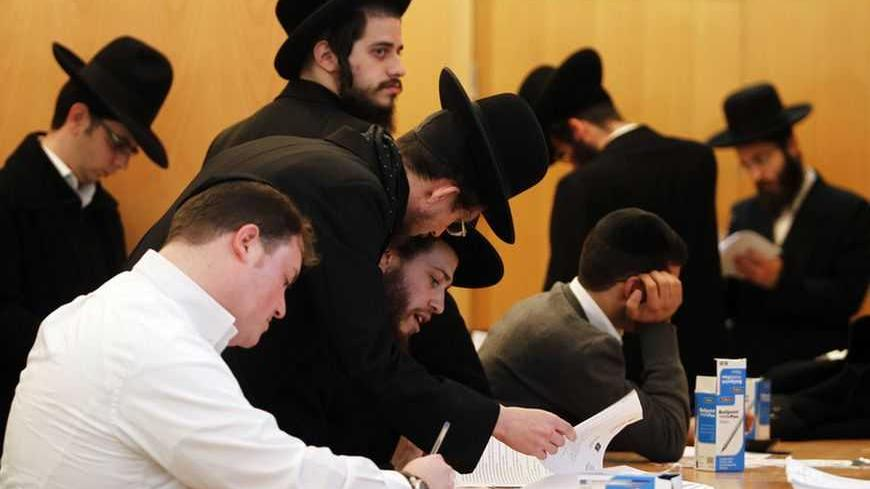 Ultra-Orthodox Jewish men sign documents at the offices of Israel's Administration for National Civil Service in Jerusalem January 6, 2013. For the first time since the August 1 expiration of the so-called Tal Law that exempted ultra-Orthodox seminary students from military conscription, dozens of scholars signed up on Sunday for alternative civilian service which, upon completion, will entitle them to avoid the draft. Some 1,300 seminary students are slated to join the program by August 2013, or until Isra