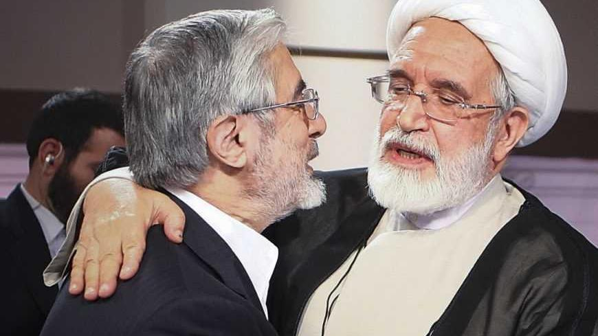 Iran's presidential election candidates Mehdi Karoubi (R) and Mirhossein Mousavi embrace after a TV debate in Tehran June 7, 2009. Iranians vote on June 12 in an election that pits hardline President Mahmoud Ahmadinejad against two moderate challengers and one fellow conservative. REUTERS/IRIB (IRAN POLITICS ELECTIONS) - RTR24F76