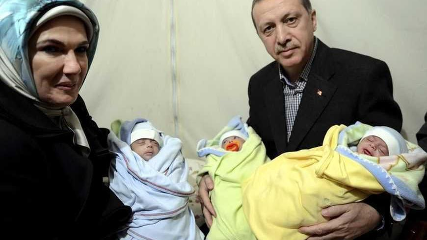 Turkish Prime Minister Tayyip Erdogan and his wife Emine Erdogan pose with Syrian refugee triplet brothers whose names are Recep, Tayyip and Erdogan as they visit a refugee camp near Akcakale border crossing on the Turkish-Syrian border, southern Sanliurfa province, December 30, 2012. REUTERS/Kayhan Ozer/Prime Minister's Press Office/Handout (TURKEY  - Tags: POLITICS CONFLICT) ) FOR EDITORIAL USE ONLY. NOT FOR SALE FOR MARKETING OR ADVERTISING CAMPAIGNS. THIS IMAGE HAS BEEN SUPPLIED BY A THIRD PARTY. IT IS