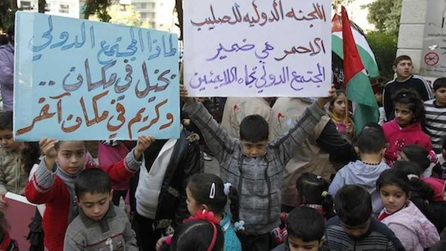 "Palestinian children who were living in the Yarmouk Palestinian refugee camp before fleeing Syria, hold up banners during a protest in front of the International Committee of the Red Cross (ICRC) in Beirut January 17, 2013. Banners read, ""The International Committee of the Red Cross is the conscience of the international community towards refugees"" (R) and ""Why the international community miserly to some places, and generous in some others?"".  REUTERS/Sharif Karim (LEBANON - Tags: SOCIETY IMMIGRATION POLITI"