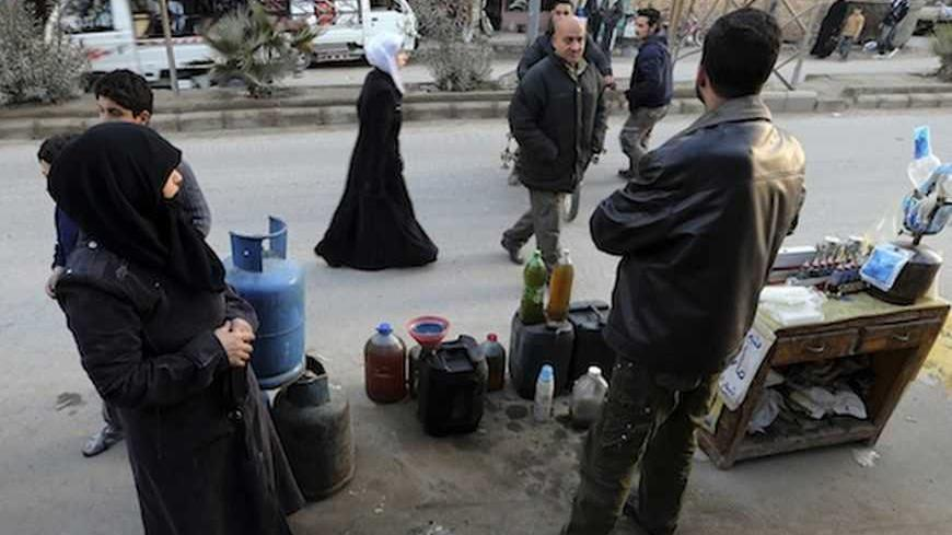A man selling petrol and gas waits for clients in Ain Tarma neighbourhood, Damascus January 23, 2013.   REUTERS/Goran Tomasevic (SYRIA - Tags: CIVIL UNREST POLITICS BUSINESS EMPLOYMENT ENERGY) - RTR3CUPA