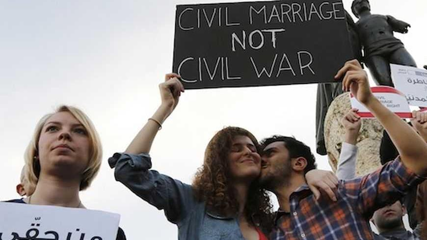 A man kisses a woman as they hold up a placard during a protest demanding to legalize civil marriage in Lebanon, at Martyrs' square in downtown Beirut February 4, 2013. Lebanese laws do not recognise civil marriages conducted in Lebanon. REUTERS/Jamal Saidi   (LEBANON - Tags: CIVIL UNREST) - RTR3DCHX