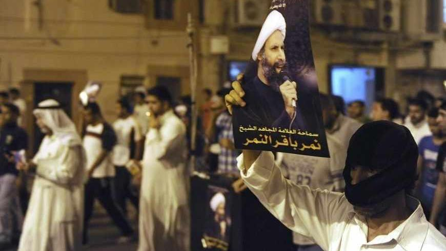 A protester holds up a picture of Sheikh Nimr al-Nimr during a rally at the coastal town of Qatif, against Sheikh Nimr's arrest July 8, 2012. Sheikh Nimr, a prominent Shi'ite Muslim cleric who was wanted by the police, was detained in Saudi Arabia's Eastern Province on Sunday over calls for more rights for the minority Muslim sect in the Sunni monarchy, his brother and an activist said. REUTERS/Stringer (SAUDI ARABIA - Tags: CIVIL UNREST RELIGION POLITICS) - RTR34QU6