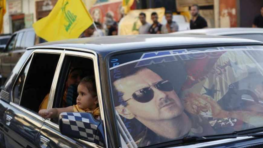 An image of Syria's President Bashar al-Assad is seen on a car's windscreen as Hezbollah supporters celebrate, after the Syrian army took control of Qusair from rebel fighters, in the Shi'ite town of Hermel June 5, 2013. Syrian government forces and their Lebanese Hezbollah allies seized control of the border town of Qusair on Wednesday, dealing a major defeat to rebel fighters battling to overthrow Assad. REUTERS/Jamal Saidi (LEBANON - Tags: POLITICS CIVIL UNREST MILITARY CONFLICT TPX IMAGES OF THE DAY) -