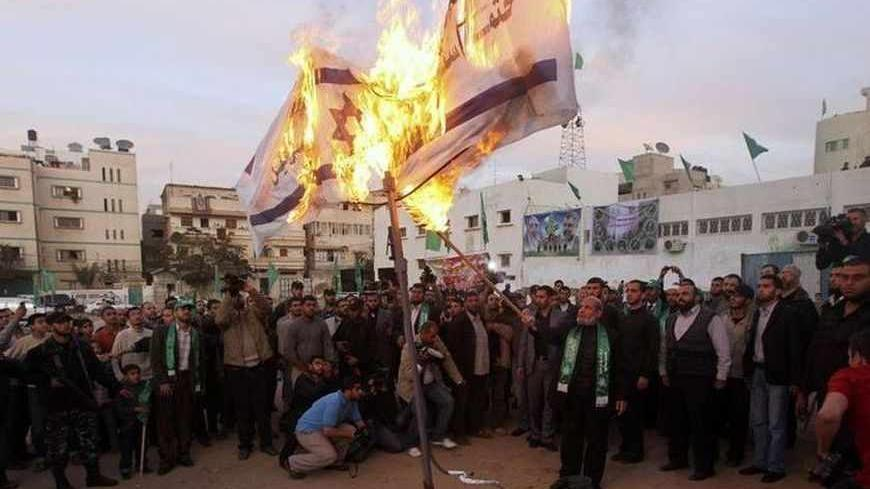 Senior Hamas leader Mahmoud al-Zahar burns Israeli flags in Gaza city in preparation for the movement's 23rd anniversary next week December 9, 2010. REUTERS/Mohammed Salem (GAZA - Tags: POLITICS ANNIVERSARY CIVIL UNREST) - RTXVKMR