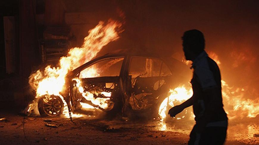 A man looks at a car on fire at the site of a bomb attack in Baghdad October 7, 2013. Bombs exploded across the Iraqi capital Baghdad on Monday, killing at least 22 people, police said. Five of the six blasts were in mainly Shi'ite Muslim districts, but there was also an explosion in the predominantly Sunni Muslim neighborhood of Doura.  REUTERS/Ahmed Saad (IRAQ - Tags: POLITICS CIVIL UNREST TPX IMAGES OF THE DAY) - RTX142ZK