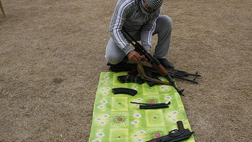 A weapons dealer checks AK-47 rifles before selling it to smugglers transferring it to Syria, at his house near the city of Mosul, 390km (240 miles) north of Baghdad, February 16, 2012. The weapons dealers sell a rifle for about $1000.  REUTERS/Stringer (IRAQ - Tags: CONFLICT) - RTR2XY8B