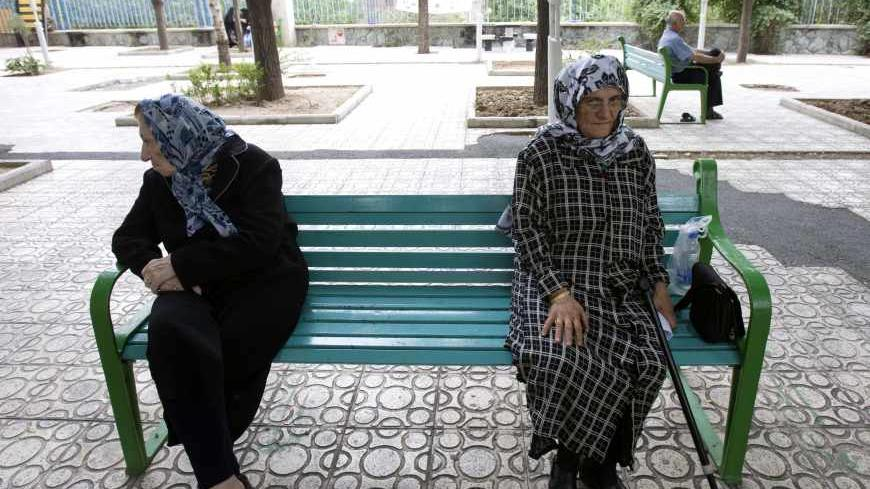 Women sit on a park bench in Tehran June 9, 2009. Iranians vote on Friday in the 10th presidential election since the 1979 Islamic revolution which toppled the U.S.-backed Shah. Three decades after the revolution, Reuters invited some older Iranians who witnessed the Shah's overthrow to look back at the changes they have lived through. To match feature IRAN-ELECTION/REVOLUTION             REUTERS/Raheb Homavandi (IRAN POLITICS ELECTIONS) - RTR24JM3