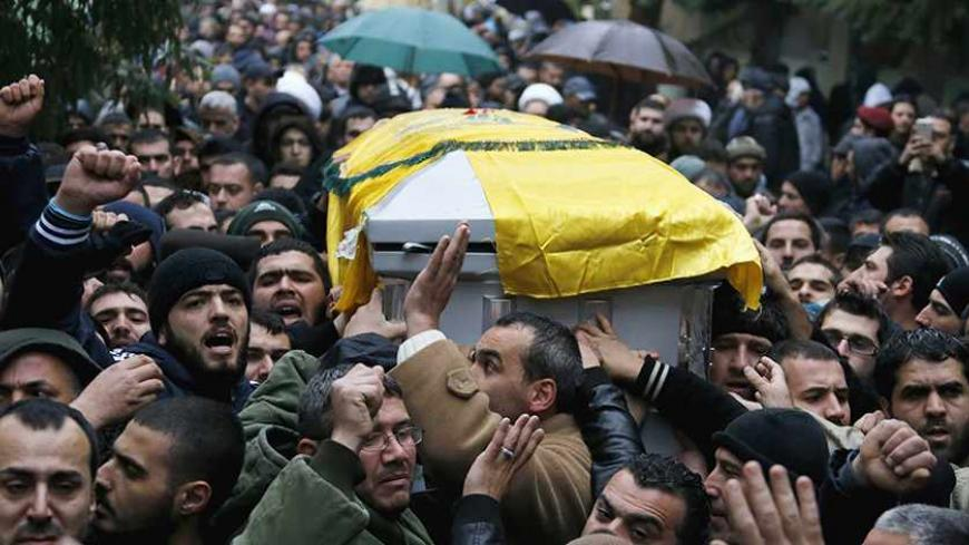 Lebanon's Hezbollah members and relatives carry the coffin of commander Hassan al-Laqqis during his funeral in Baalbeck, in Lebanon's Bekaa valley December 4, 2013. Al-Laqqis, a Hezbollah commander who fought in Syria's civil war was shot dead outside his home in Lebanon on Wednesday in an attack which the militant Shi'ite group blamed on Israel. Israel denied any role in the killing of Hassan al-Laqqis, who was shot from close range by a silenced gun as he arrived home at around midnight in the Hadath dist