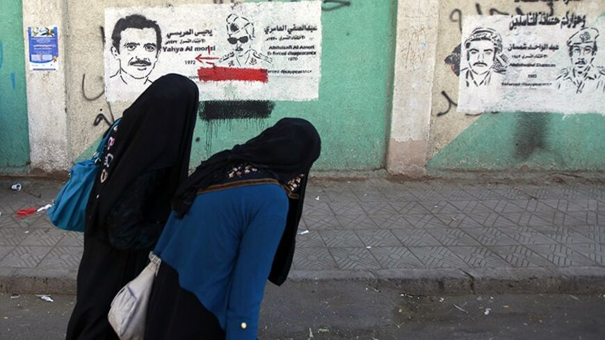 Women walk by a mural of a flag of the Yemen Arab Republic from former North Yemen in Sanaa, December 24, 2013. REUTERS/Mohamed al-Sayaghi (YEMEN - Tags: POLITICS SOCIETY) - RTX16T8G