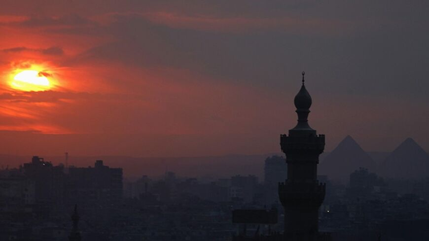 The sun sets on the minarets and the Great Pyramids of Giza (R) in Old Cairo December 31, 2013. REUTERS/Amr Abdallah Dalsh  (EGYPT - Tags: CITYSCAPE SOCIETY TPX IMAGES OF THE DAY) - RTX16Y9H