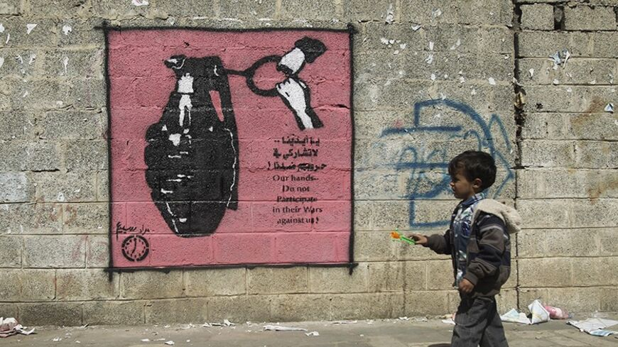 A boy walks past a graffiti depicting a grenade on a street in Sanaa January 9, 2014. The paint is part of a graffiti campaign against armed conflicts in Yemen. REUTERS/Khaled Abdullah (YEMEN - Tags: POLITICS CIVIL UNREST SOCIETY) - RTX177LM