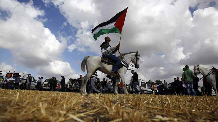 An Arab-Israeli protester on a horse holds a Palestinian flag during a march in support of the right of return for Palestinian refugees who fled their homes or were expelled during the 1948 war that followed the creation of the state of Israel, near the Arab-Israeli town of Umm al-Fahm April 16, 2013.      REUTERS/Ammar Awad (ISRAEL - Tags: CIVIL UNREST ANIMALS POLITICS TPX IMAGES OF THE DAY) - RTXYO2G