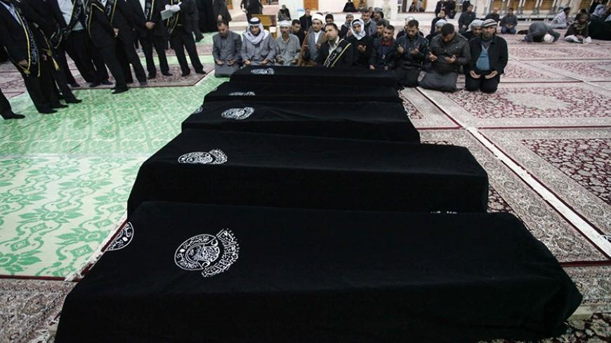 Mourners pray near the coffins of victims killed by a bomb attack at a Shi'ite Muslim village near the Iraqi city of Baquba, during a funeral at the Imam Ali shrine in Najaf, 160 km (100 miles) south of Baghdad, January 25, 2014. Police said that at least six people were killed on Saturday when three mortar bombs hit the village. REUTERS/ Alaa Al-Marjani   (IRAQ - Tags: CIVIL UNREST POLITICS CONFLICT) - RTX17U8H