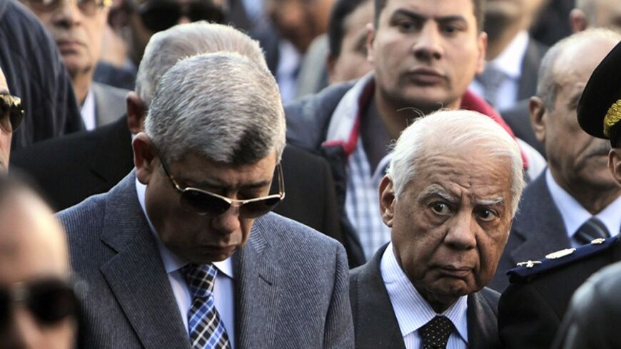 Egypt's Interior Minister Mohamed Ibrahim (L) and Prime Minister Hazem el-Beblawi walk during the funeral service of General Mohamed Saeed, head of the technical office of the minister of interior, with police and Saeed's relatives in Cairo January 28, 2014. Gunmen on a motorbike killed Saeed outside his home in Cairo on Tuesday, putting pressure on the military-backed government as it struggles to contain an Islamist insurgency.  REUTERS/ Mohamed Abd El Ghany (EGYPT  - Tags: POLITICS CIVIL UNREST) - RTX17Y